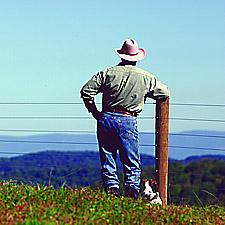 Man standing at a fence with mountains in the distance